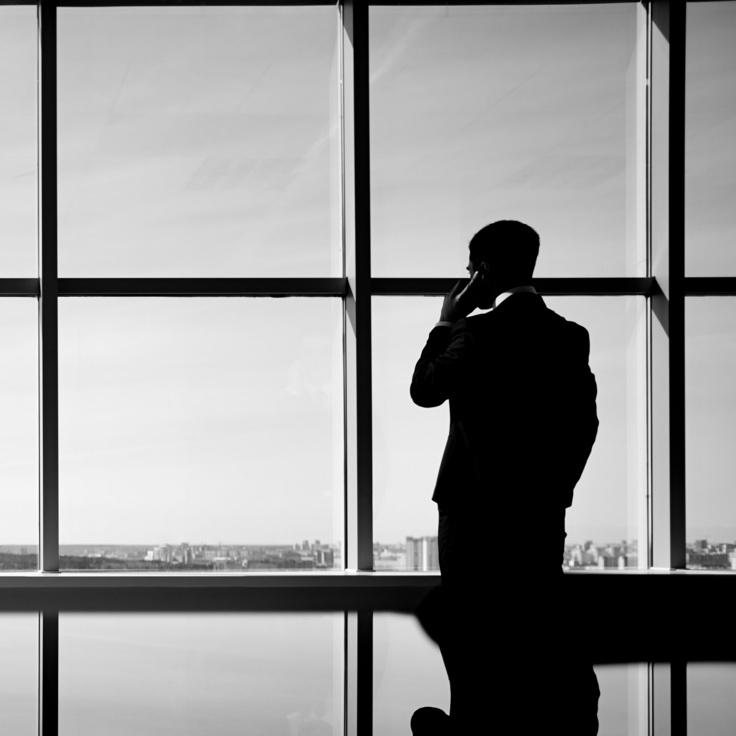 Man_in_phone_looking_out_window_grey_736.jpg